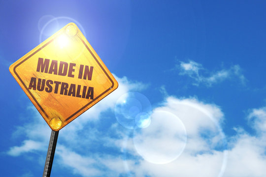 Yellow road sign with a blue sky and white clouds: Made in austr