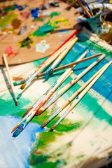 Used brushes in the vase near picture with an artist's palette of colorful oil paint for drawing and painting lying on the grass