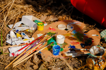 Used brushes with an artist's palette of colorful oil paint for drawing and painting lying on the grasscolorful oil paint for drawing and painting lying on the grass
