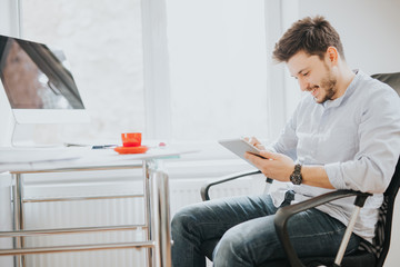 Young man in a modern bright office on sunny day sketching construction project on a tablet and drink coffee