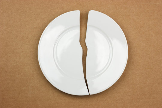 Broken plate on cardboard background