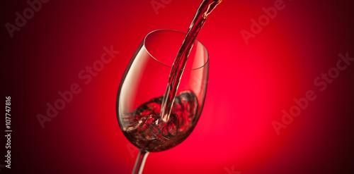 Vino Rosso Versato In Bicchiere Su Sfondo Rosso Stock Photo And