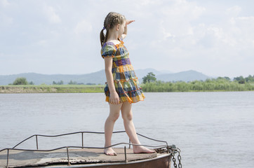 A girl stands on a boat