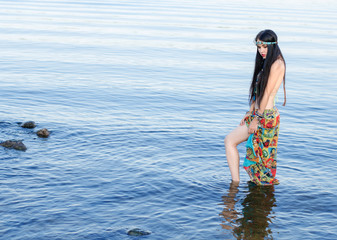 Beautiful slim woman with long black hair and a bandage on his head, in the clothes in boho style, standing in water.  Boho chic style