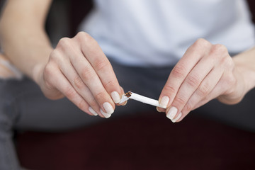 Close up of woman hands with broken cigarette. Stop smoking concept