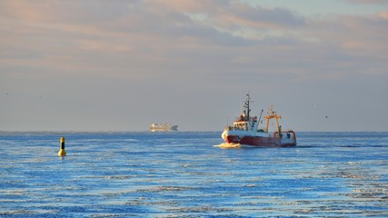 Frozen fishing vessel in comming back to the port at the sunset