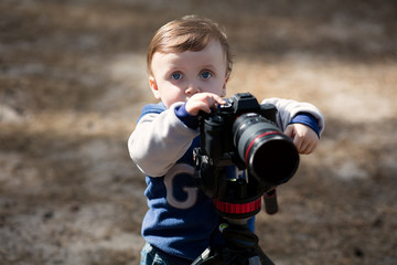 Young photographer child taking photos with camera on a tripod