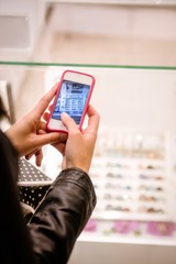 Close-up of womans hand clicking a photo of shop display