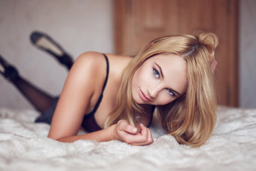 Sensual blonde woman posing on bed
