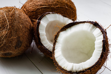 Whole and broken coconut on the white plank table.