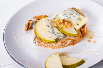 Sandwich with Blue cheese with slices of pear, nuts and honey on plate.