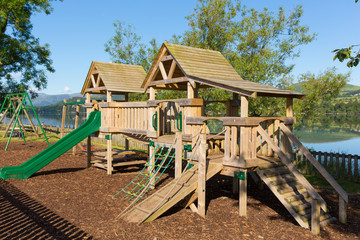 Wooden climbing frame for children in rural outdoor location by a lake