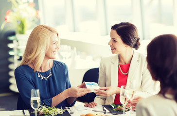 happy women giving birthday present at restaurant
