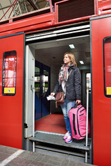 Woman tourist with suitcase coming out of train at station