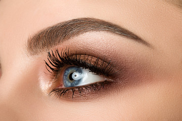 Close-up of woman eye with beautiful brown smokey eyes makeup