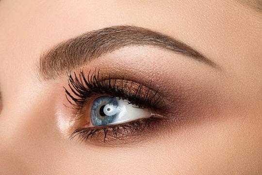Close-up of woman eye with beautiful brown smokey eyes makeup