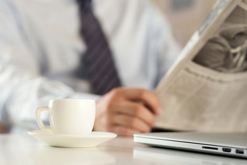 Cup of coffee with businessman reading newspaper on background