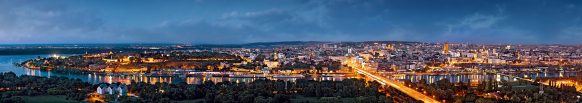Belgrade panorama by night, Danube and Sava rivers confluence, city lights with blue cloudy sky