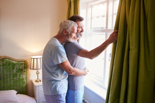 Side view of couple embracing while looking through window