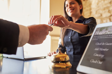 Guest takes room key card at check-in desk of hotel, close up Wall mural