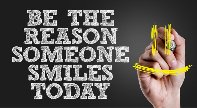 Hand writing the text: Be The Reason Someone Smiles Today