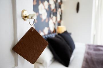 Key And Wooden Fob In Door Of Hotel Bedroom