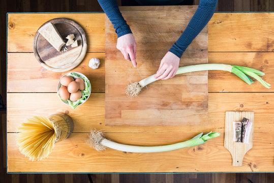 Preparing carbonara's pasta. Female hands preparing the leek.