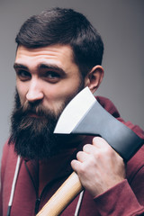 Shaving with axe. Portrait of Confident young bearded man carrying a big axe on shoulder and looking at camera while standing against grey background