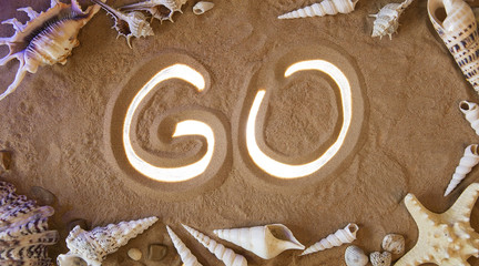 hand-drawn Go symbol in the sand. Beach background. Top view
