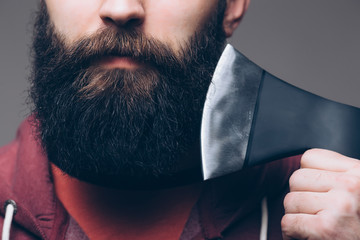 Close up of beard Confident young bearded man carrying a big axe on shoulder and looking at camera while standing against grey background
