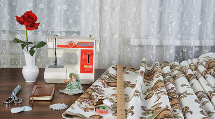 workplace оf seamstress with the sewing machine and retro fabri