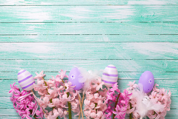 Decorative violet eggs  and pink hyacinths flowers on turquoise