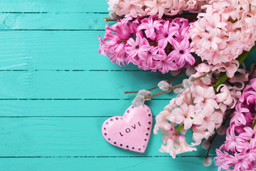 Background with  pink hyacinths  and  decorative heart  on  turq