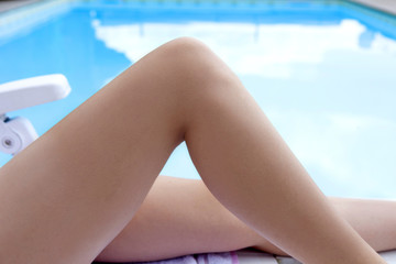Body part - Legs of a young woman relaxing near a swimming pool
