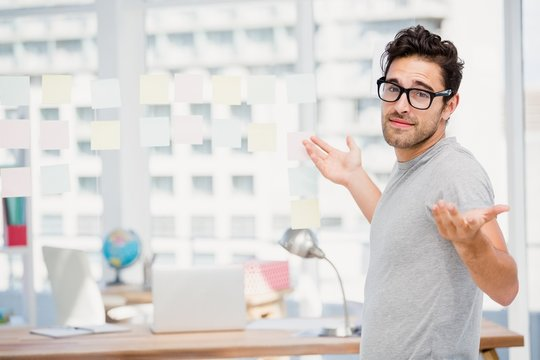 Man shrugging his shoulder in office