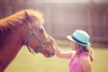 Pony Standing with Little Girl Outside
