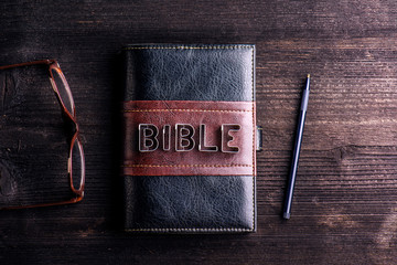 Bible, eyeglasses and pen laid on old wooden table