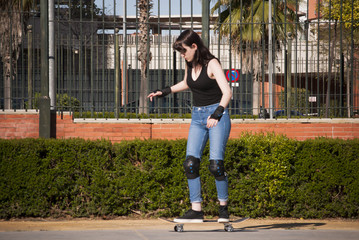 Beautiful young woman practicing with the skateboard on the stre