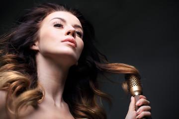 Modelowanie włosów na szczotce.Długie zdrowe i lśniące włosy, długie kobiece włosy.