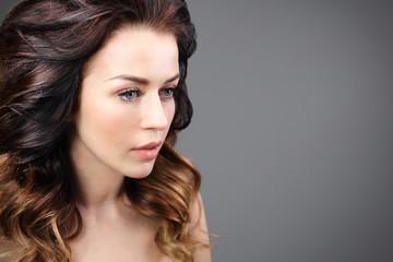 Stylizacja włosów, kobieca fryzura. Portret pięknej kobiety na czarnym tle.