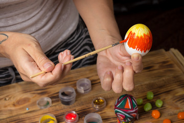 process of paiting easter egg with orange brush, cans, wood