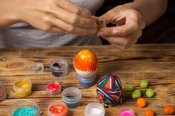 girl sprinkle glitters on easter egg, creating holiday painted decorations