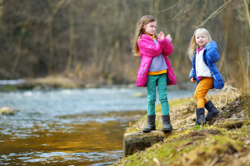 Two cute little sisters having fun by a river