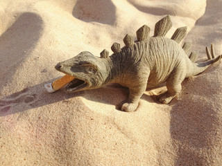 Toy in the form of a dinosaur standing on the sand eating butt of a cigarette. Holidays photo.