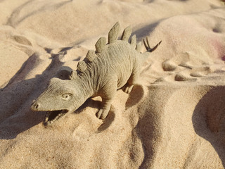Toy in the form of a dinosaur standing on sand. Holidays photo.