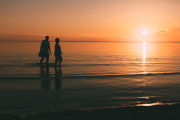 Silhouette of adult couple which costs in the sea and holds in hand footwear against a sunset.