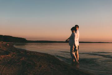 Adult couple walks on the seashore. Back view.