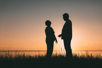 Adult couple silhouettes at sunset. Evening photo.