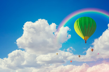 colorful hot air balloons and rainbow with cloudy blue sky background