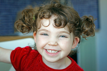 Portrait of adorable young cute girl with hair tufts, laughing and smiling.